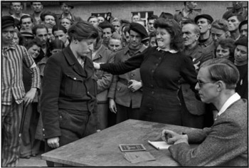 April 1945, in Germany, Dachau. A young Belgium woman is identified as a former Gestapo informant, while she was hiding in the crowd of a transit camp. | HENRI CARTIER-BRESSON/Magnum